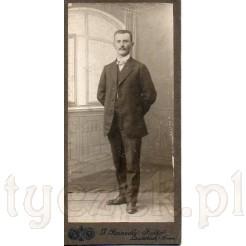Dystyngowany, elegancko ubrany mężczyzna stojący przy uchylonym oknie na dawnym zdjęciu
