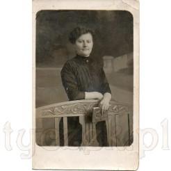 Kobieta z książką stojąca przy drewnianym, stylizowanym meblu na pamiątkowej fotografii