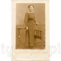 Dystyngowana dama stojąca przy bardzo stylowych meblach: fotelu Art Deco oraz stoliku ludwikowskim