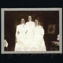 Trzy panny w białych sukienkach pozujące do zdjęcia