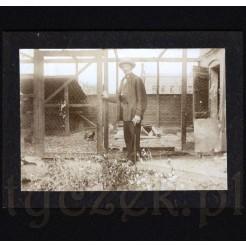 Starszy pan stojący przy kurniku na pamiątkowym zdjęciu