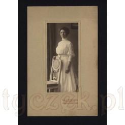 Kobieta w bieli przy bardzo stylowym krześle z oryginalnym oparciem na pamiątkowej fotografii