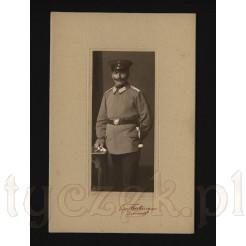 Niemiecki żołnierz w pełnym umundurowaniu na pamiątkowym zdjęciu wykonanym w atelier