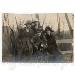 Cztery elegancko ubrane damy w gustownych kapeluszach podczas spaceru w parku