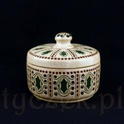 Efektowna bomboniera z oryginalną pokrywką wykonana została z ceramiki w kremowym odcieniu