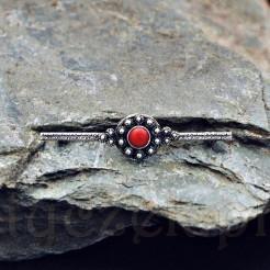 Podłużna broszka z centralnie umiejscowionym medalionem w kształcie kwiatu. Środek w formie kaboszonu z czerwonego korala zwanego kwiatem oceanu