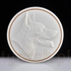 Porcelanowa broszka z wizerunkiem owczarka niemieckiego.