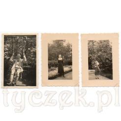 Mężczyzna huśtający się na huśtawce, elegancka dama w parku oraz kobieta z dzieckiem na parkowej alejce