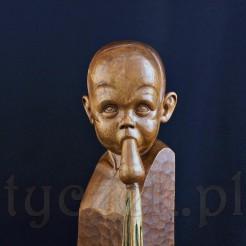 Oryginalna drewniana rzeźba przedstawiająca dziecko jedzące marchewkę