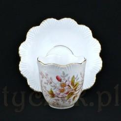 Czarka filiżanki w centralnym miejscu ozdobiona została kompozycją kwiatu jabłoni wraz z gałązkami i liśćmi