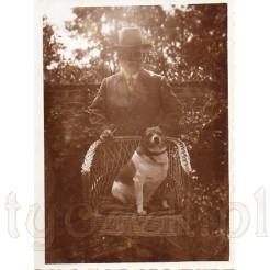 Pan z siedzącym na fotelu psem na pamiątkowej fotografii