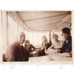 Grupa znajomych siedzących w restauracji na dawnej czarno białej fotografii