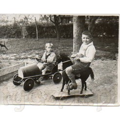 Chłopcy ze swoimi zabawkami: blaszanym samochodzikiem i koniem na podeście z kółeczkami