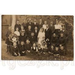 Goście pary młodej na tle starej kamienicy na pamiątkowym zdjęciu