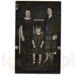 Trzy młode panny pozujące w stylowym wnętrzu na pamiątkowej fotografii