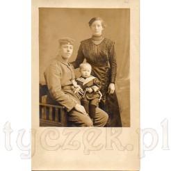 Żołnierz w mundurze ze swoim synkiem i kobietą na pamiątkowym zdjęciu