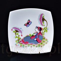 Wielobarwny wizerunek kobiety wśród kwiatów, nad którą lata motyl zdobi czworoboczne naczynie z białej porcelany