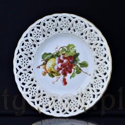 Dojrzała kiść fioletowych winogron oraz zielone jabłko zdobi ten owocowy talerzyk