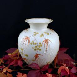 Orientalne kwiaty o pomarańczowej barwie oraz ozdobne tłoczenia zdobią pulchny brzusiec wazonu