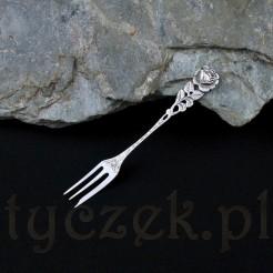 Srebrny widelec deserowy ozdobiony został płaskorzeźbionym kwiatem róży w rozkwicie